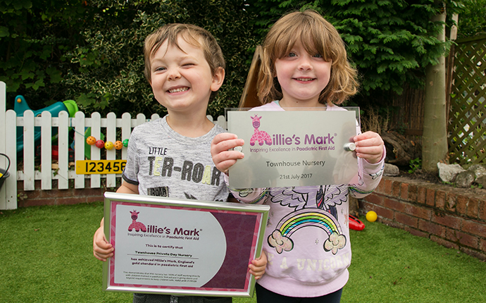 Children at Townhouse Private Day Nursery holding a certificate and plaque